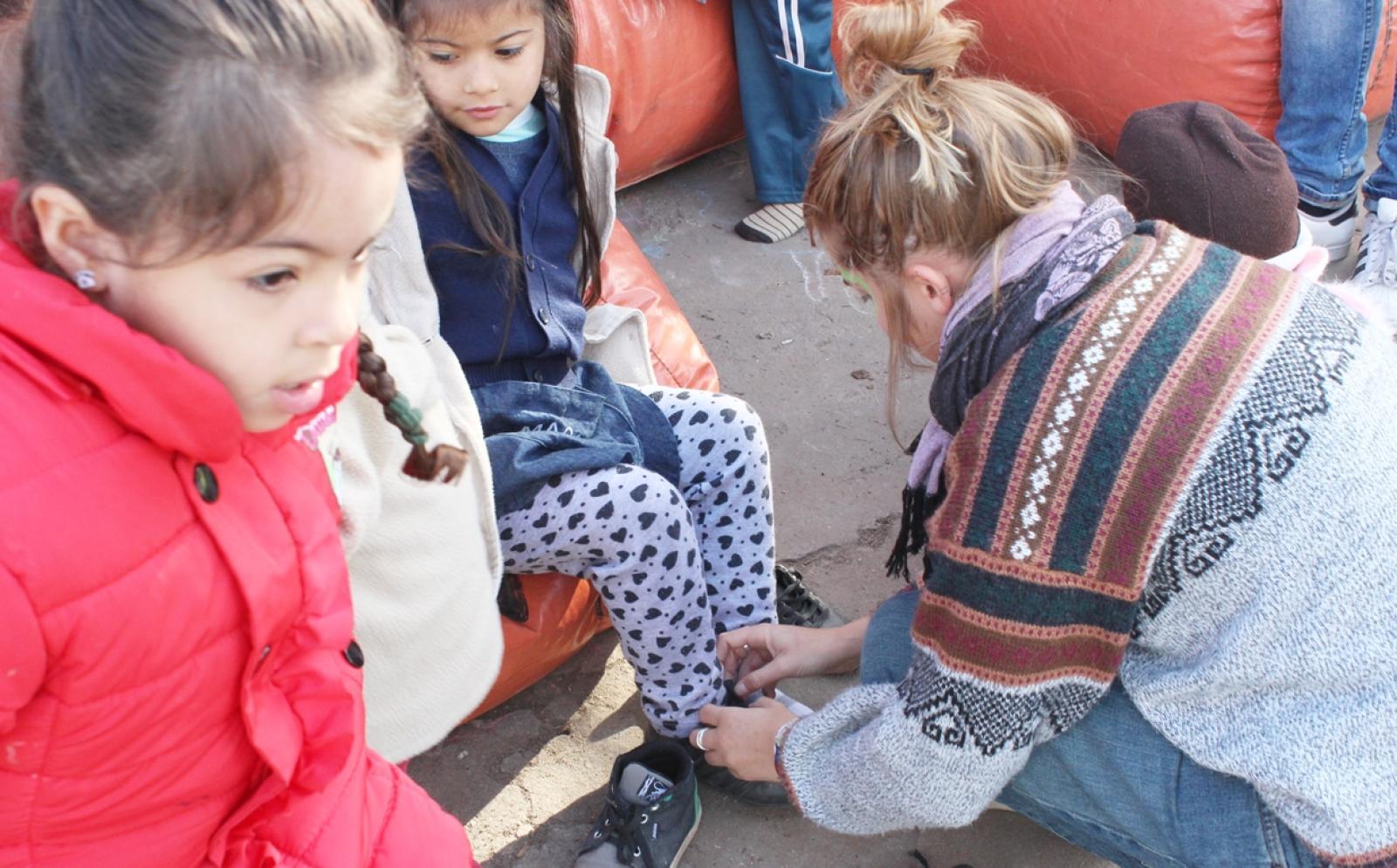 アルゼンチンの子供の靴紐を結ぶ高校生ボランティア